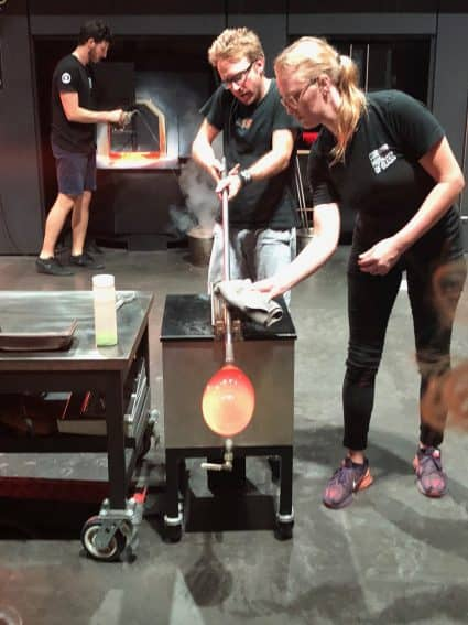 Glassblowing artists at the Corning Museum of Glass in Corning, NY craft a piece in front of an audience.