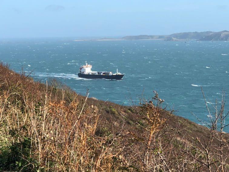 Cargo ship navigates the windy harbor toward the island of Herm.