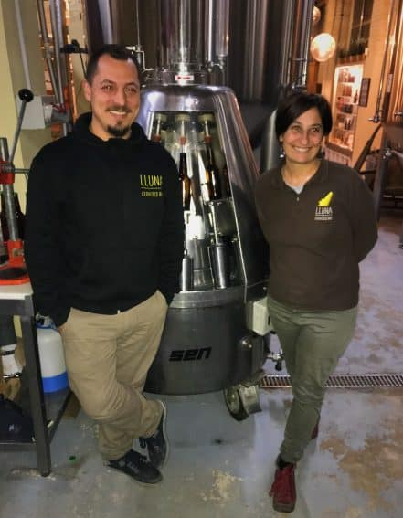 The owners of Cerveses Lluna, Maria Vicente and David Seguí, are shown gleaming next to the machine that bottles their organic beer. Photo by Olivia Gilmore.