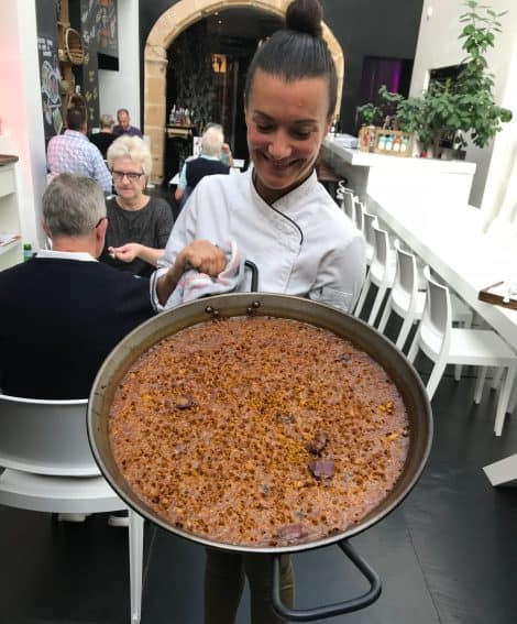 "The owner of La Seu in Dénia holding her freshly cooked ""Arroz a Banda,"" a traditional dish made with a variety of seafood and rice."