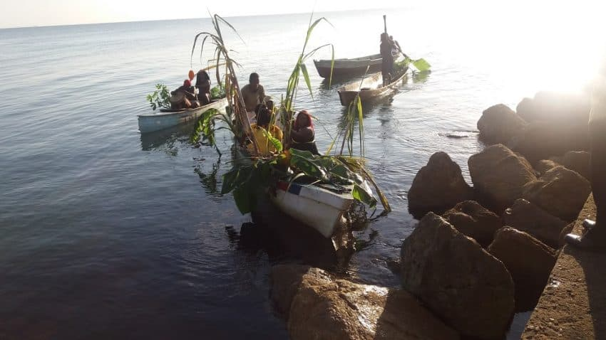 Boats arrive onshore with their native participants in the annual reenactment of Garifuna Settlement Day