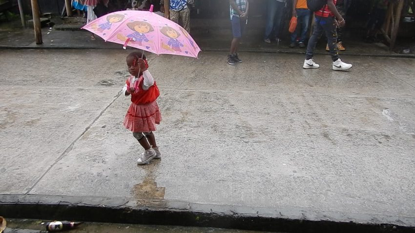 A young girl in pink marches as her own entry in the rain-sodden Guatemala Settlement Day Parade in 2016.