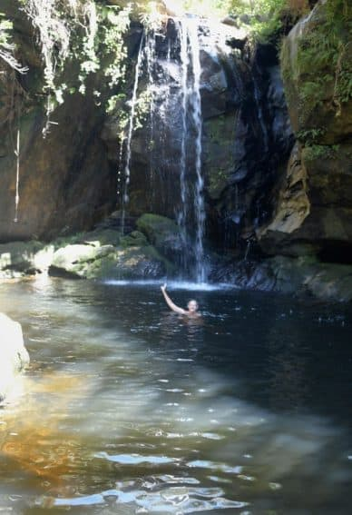 Enjoying a dip below a waterfall after a hike in Madagascar, East Africa.