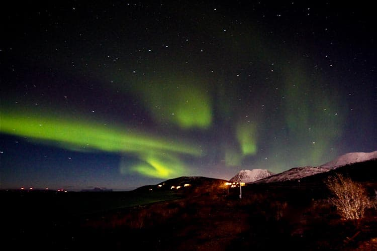 Wine and dine by the fireplace - with a little photography - and the northern lights over the fjord at Lyngen Experience.