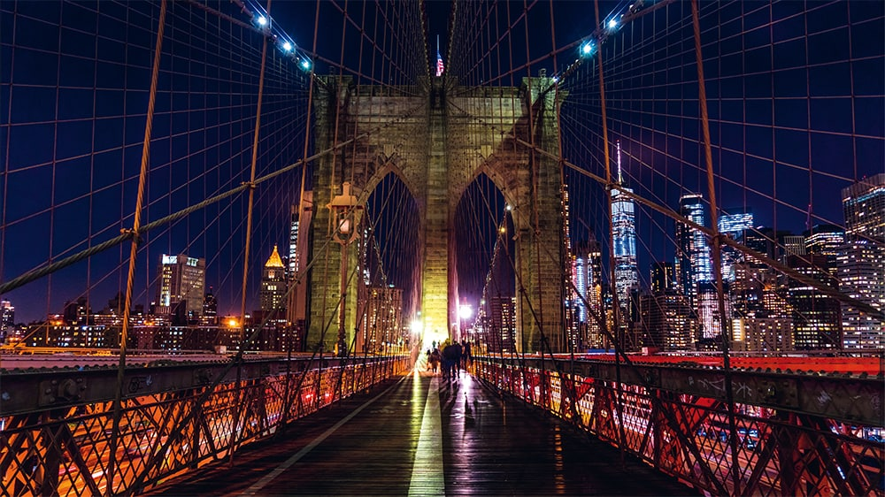 The Brooklyn Bridge across the East River, which connects Manhattan and Brooklyn, symbolizes the transition to a better life.