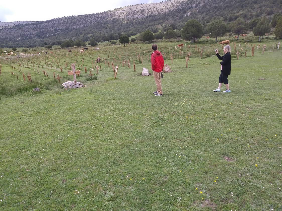Tourists snap pictures of the restored Sad Hill Cemetery as cows roam the open field.