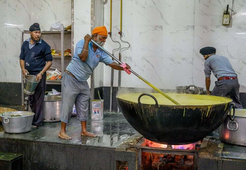 It is challenging work cooking in massive woks while standing barefoot on the hot surface atop the cooking platform.