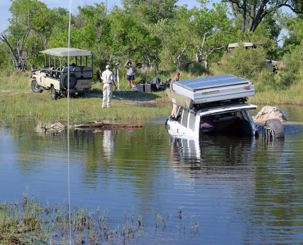 A safari 4x4 in the drink crossing a river.