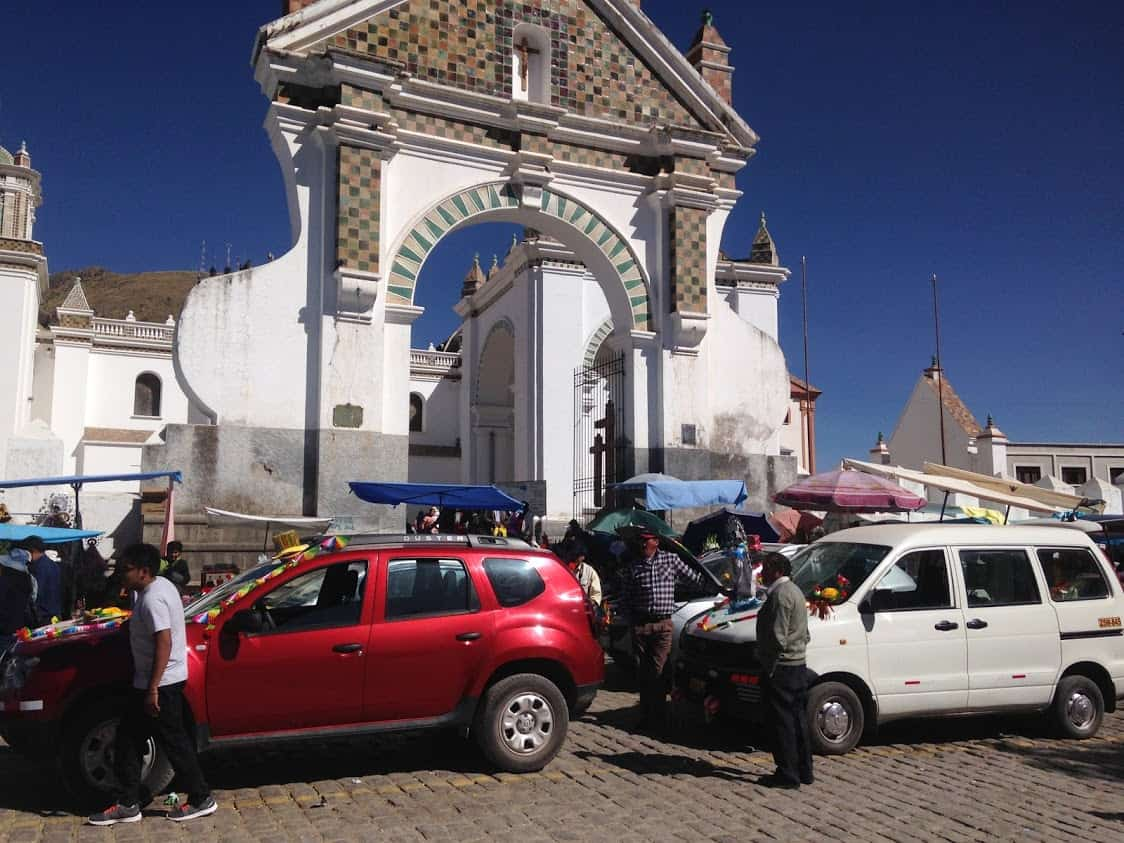 Cars decked out in vibrant decorations block the crowded streets while they wait.