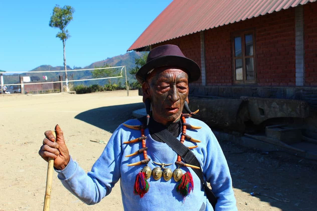 One of the former headhunters of Nagaland walking around the village. He wears horns in both ears and the typical necklace.
