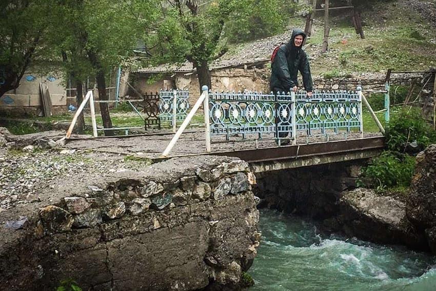 Hiking Tajikistan: Crossing a bridge in the pouring rain in the mountains.