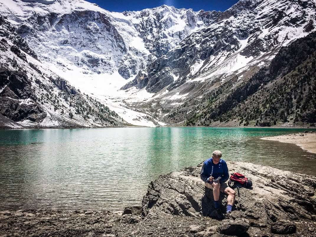 Hiking Tajikistan: The author takes notes on the trail near Kulikalona, Tajikistan. John Henderson photos.