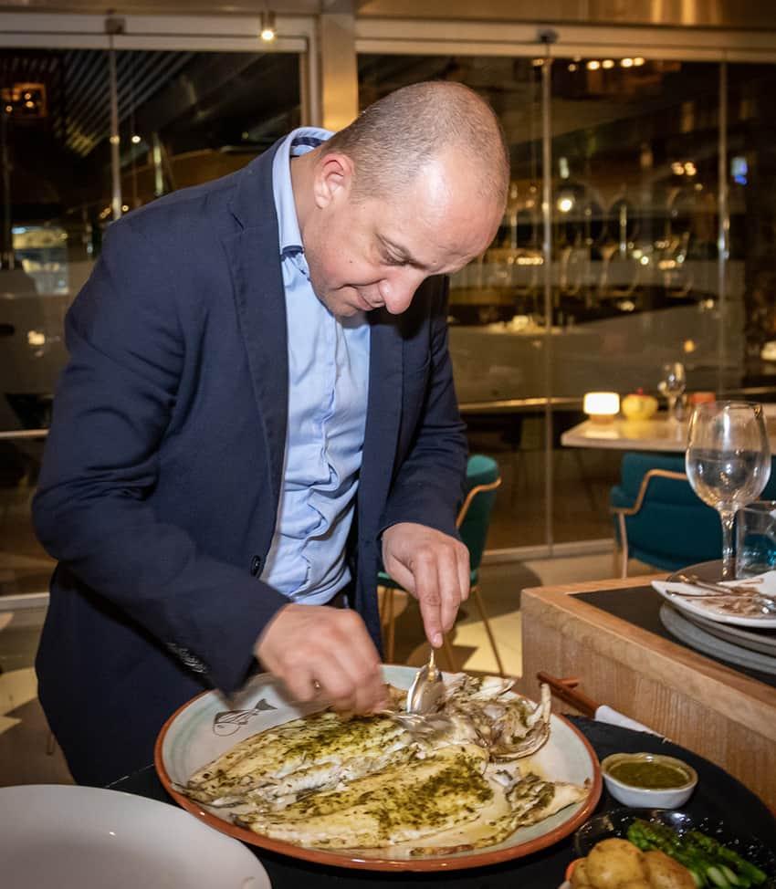 Preparing grilled sea bass with lemon chermoula sauce at Baiben restaurant
