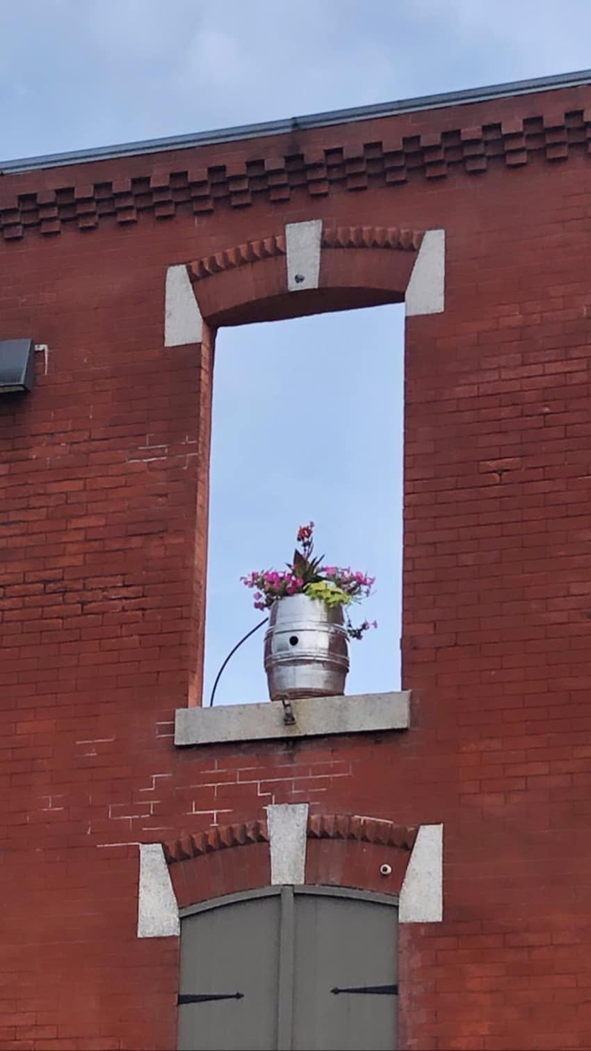 Window frame adorned with flowers at Philadelphia Brewing Company.