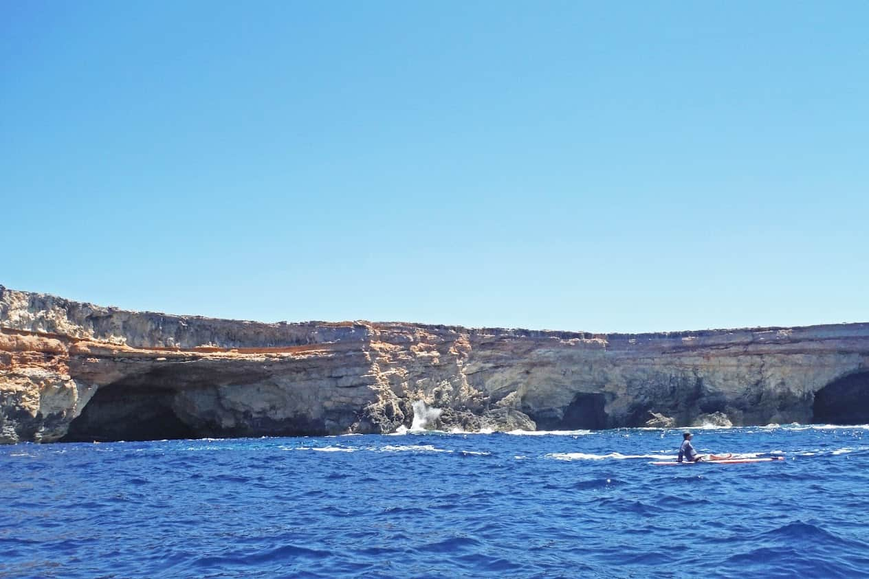 Taking a rest on a stand up paddle board alongside some of the many rocky caves that dot the island of Ibiza