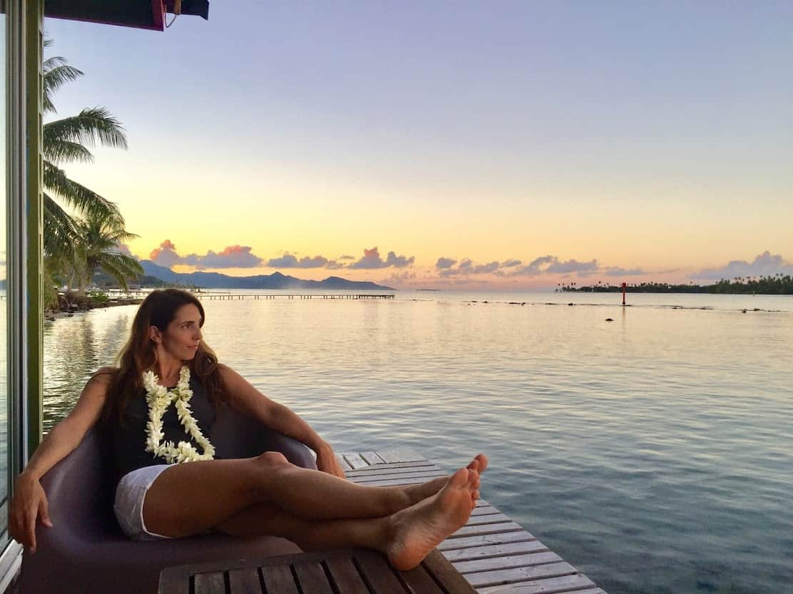 Michelle contemplating the sunset at Granda Maeva's overwater bungalow guesthouse on Raiatea.