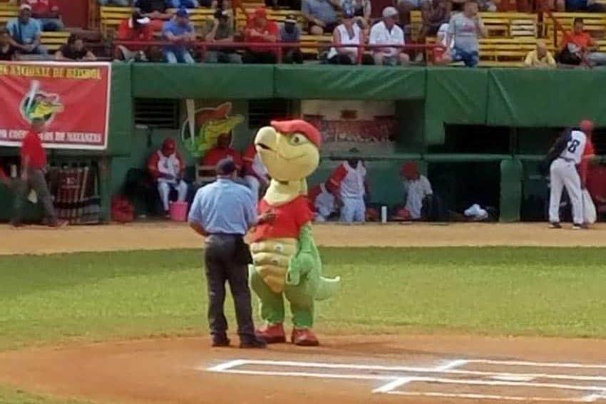 A mascot and an umpire at a Cuban baseball game.