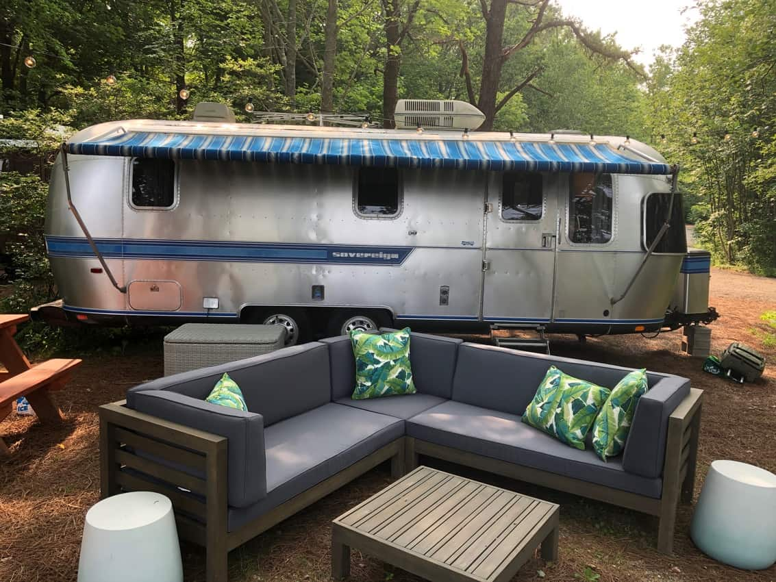 One of the sites at Sandy Pines is an old Airstream trailer with outdoor furniture around a firepit.
