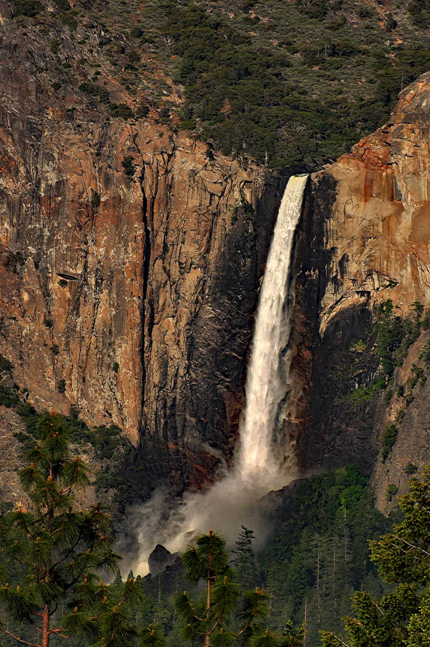 Waterfalls engorged with spring snowmelt send up a smoke-like spray when they hit the valley floor.