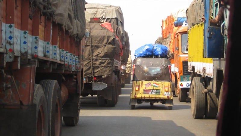 A rickshaw squeezing between trucks at the Rickshaw Run