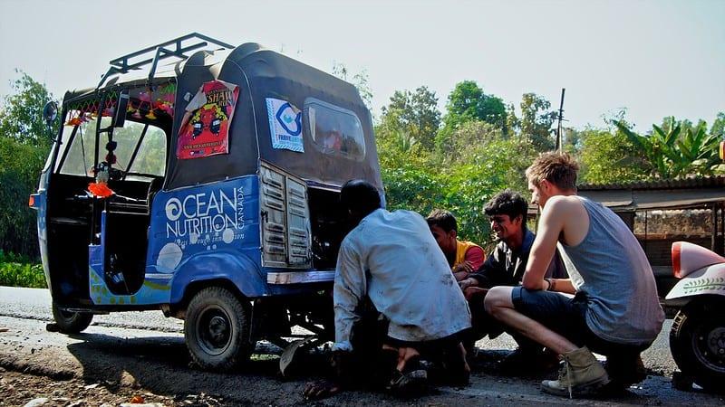 Rickshaw Run participants and local trying to diagnose a broken down rickshaw
