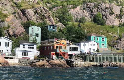 The colorful harbor of St Johns, with old fishing shacks and docks.
