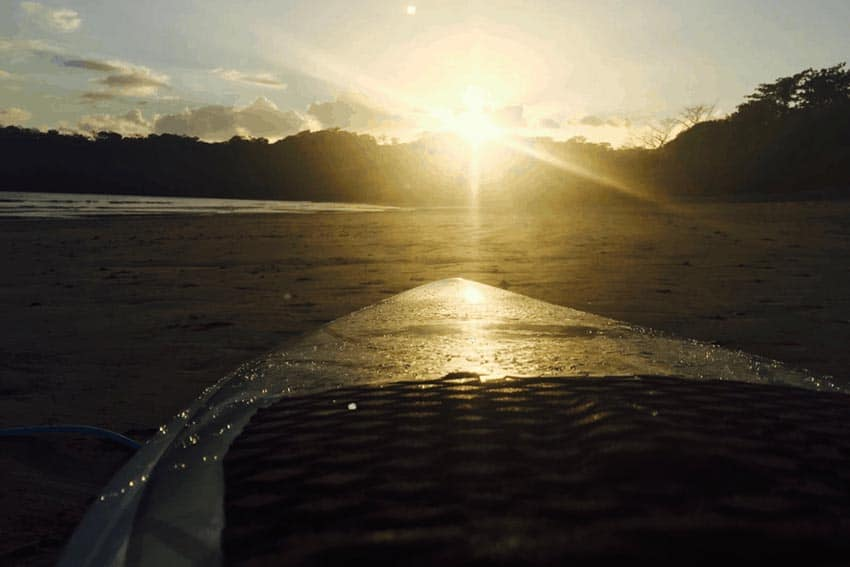 The setting sun glistens off of a surfboard in Panama.