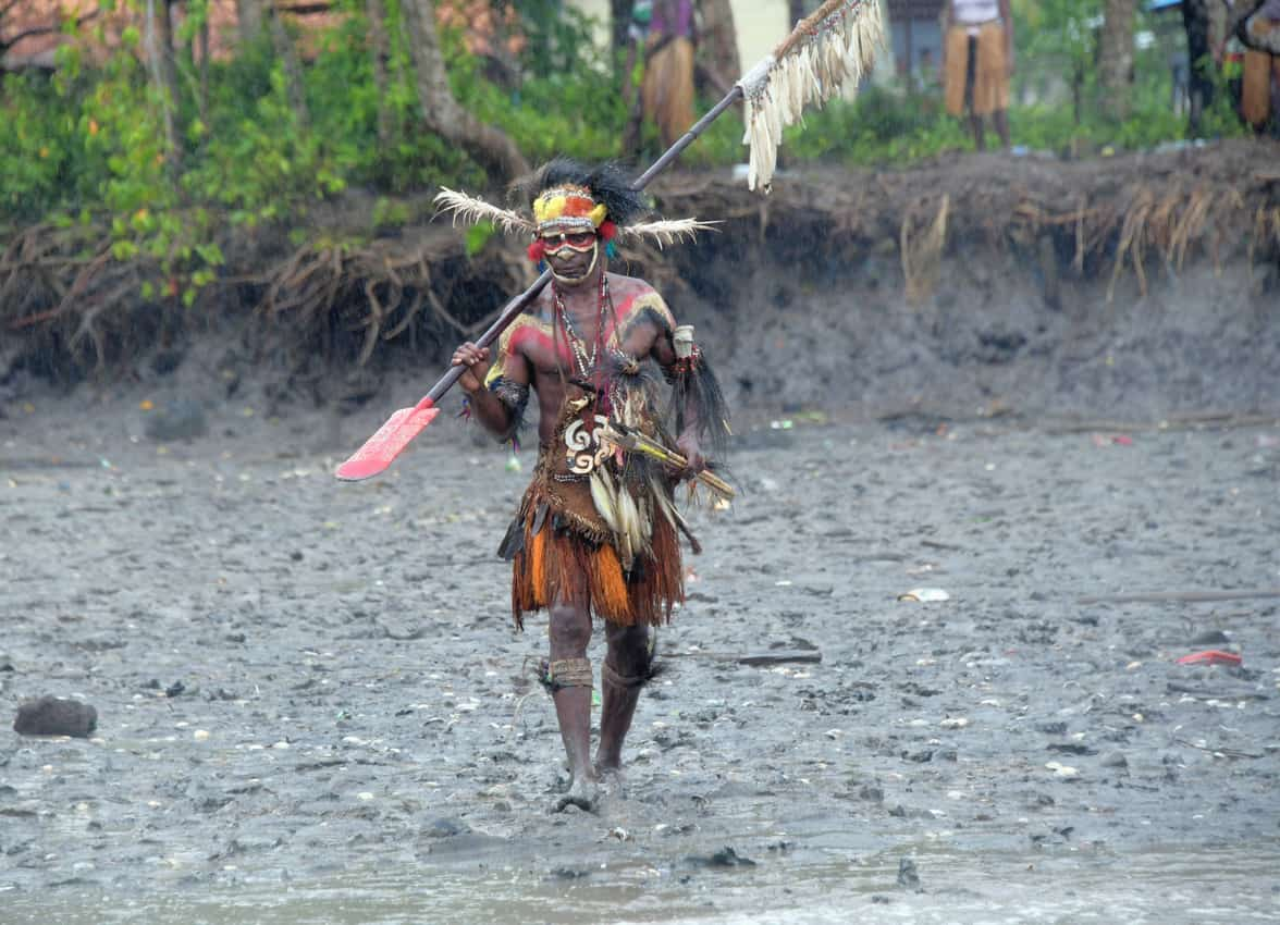 Traditionally dressed Asmat walks to his canoe. Tab Hauser photos