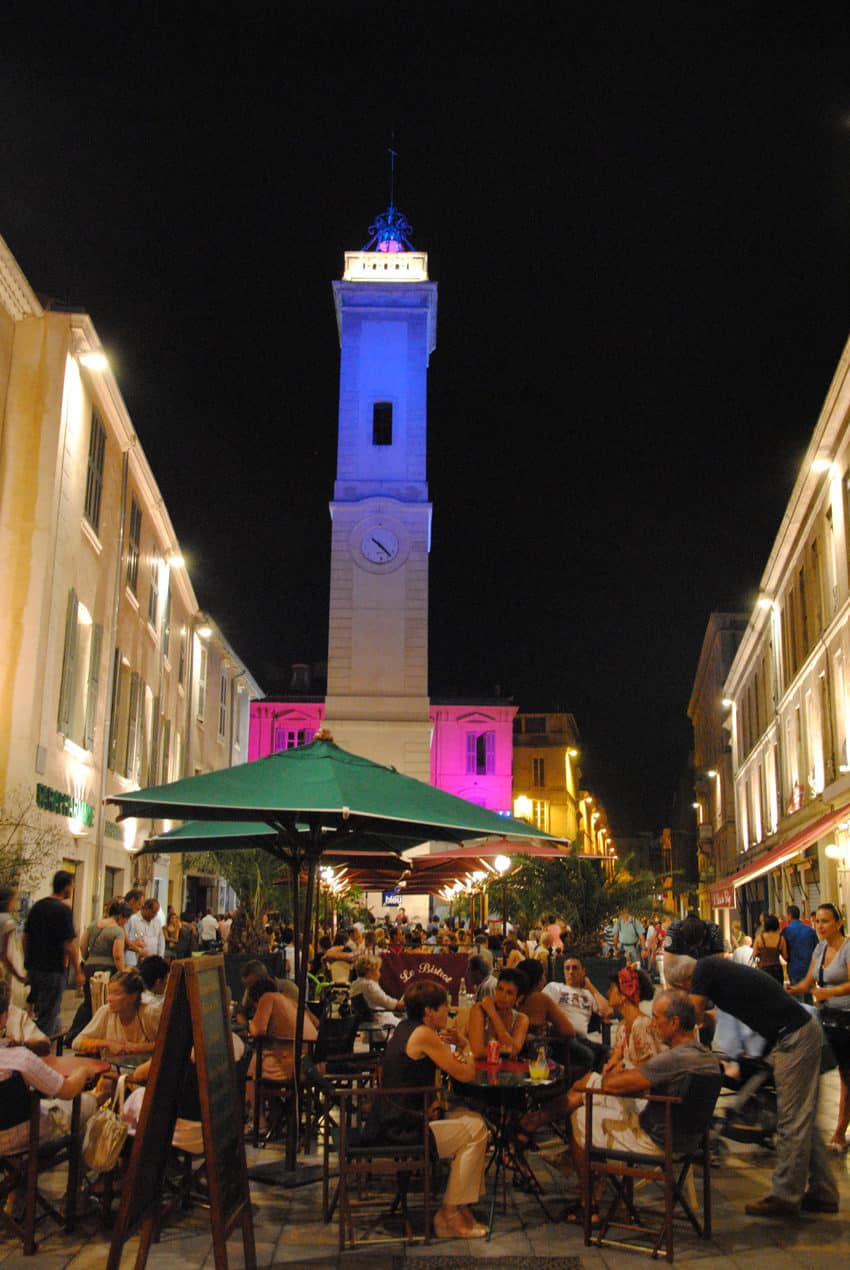 The busy Place de l'Horloge at night in the centre of Nimes.