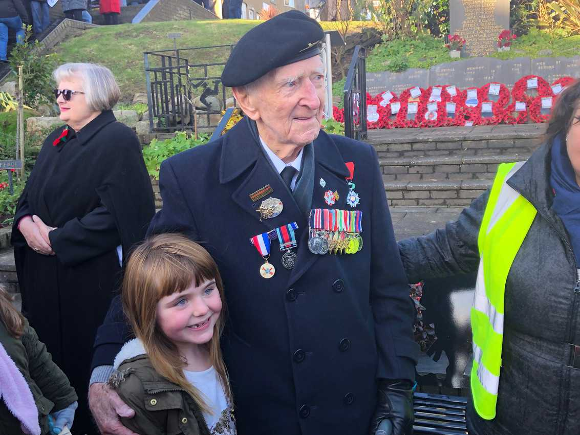 A veteran poses with a local girl at the Veteran's Day ceremony on the Isle of Man.