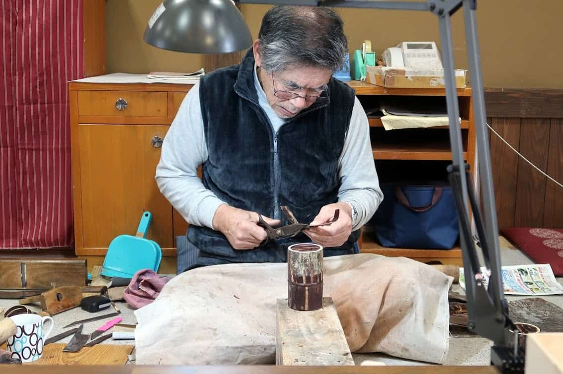 A craftsman works his trade in kabazaiku, applying strips of cherry bark to tea canisters and other products at Kakunodate Denshokan