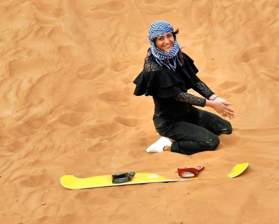 A young Dubai woman wipes out on a sand board