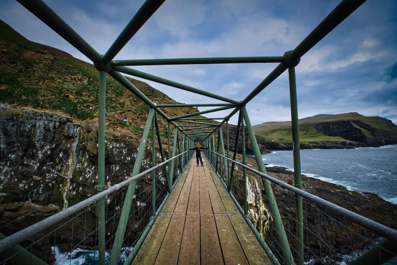 Patri crossing a bridge in Mykines, Faroe Islands.