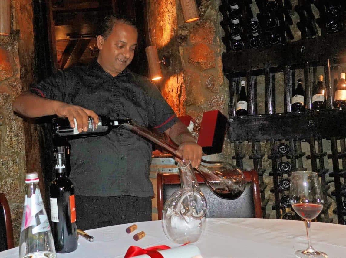 The sommelier decants fine red wine in the cellar JA Manafaru, Maldives.