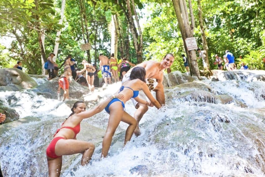 Proceed with caution when approaching the top of the falls, as it can be slippery along the rocks at Dunn's River Falls, Jamaica, Caribbean. Sandals photo.