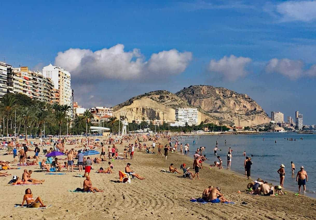 A long stretch of beach draws sunbathers in Alicante.