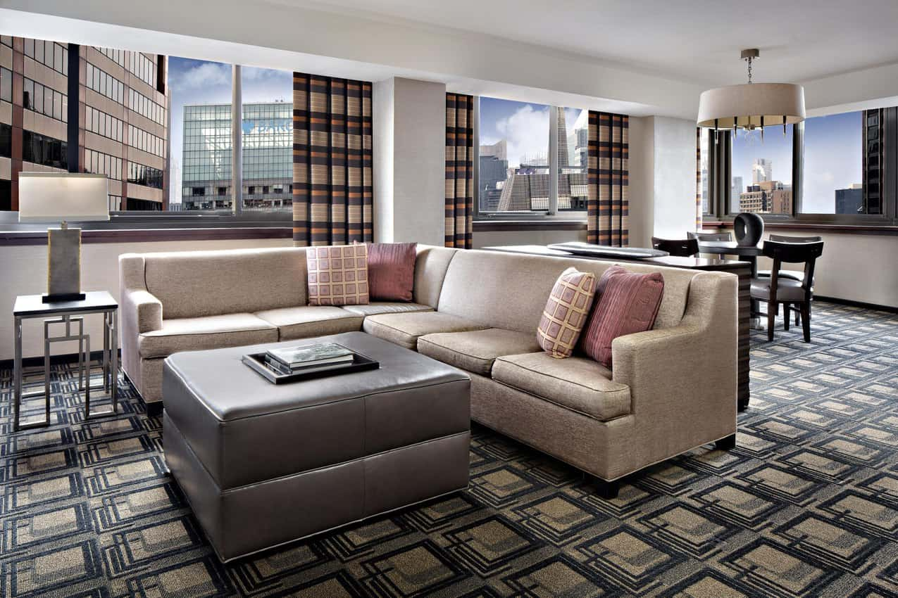 With comfortable couches, a fullsize table, and a long hallway, this Sheraton hotel suite feels like an apartment.