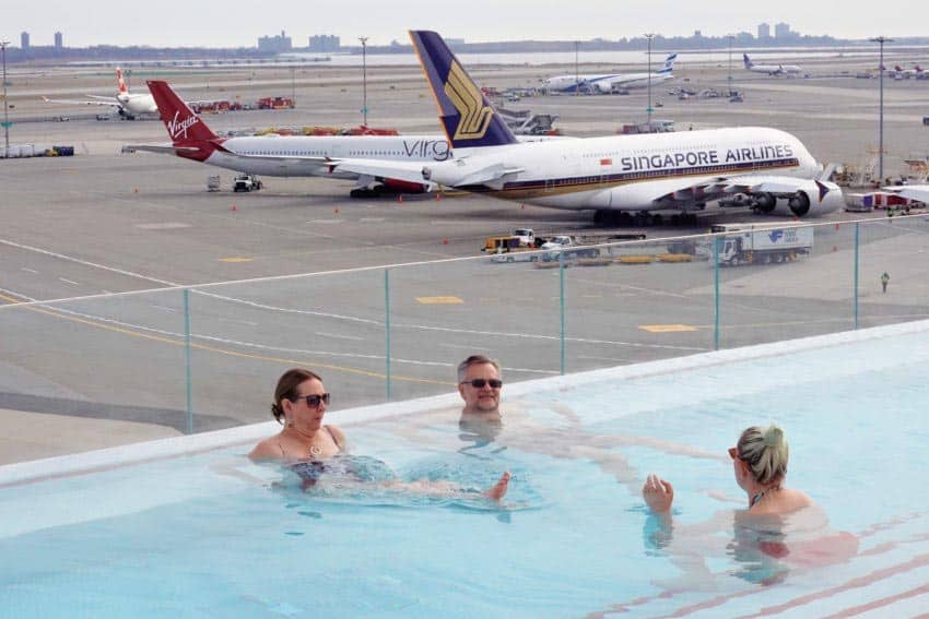 Guests wade in the heated rooftop pool with a Singapore Airlines A380 in view.