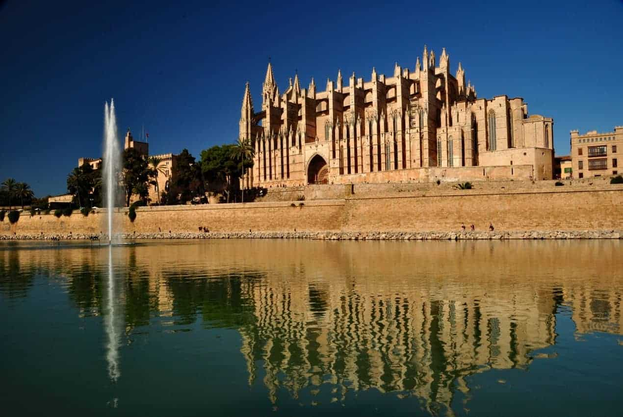 In Palma de Mallorca, the cathedral is a mix of architectural and artistic styles inside and out. The exterior and its reflection are best viewed from Parc de la Mar steps from the waterfront.