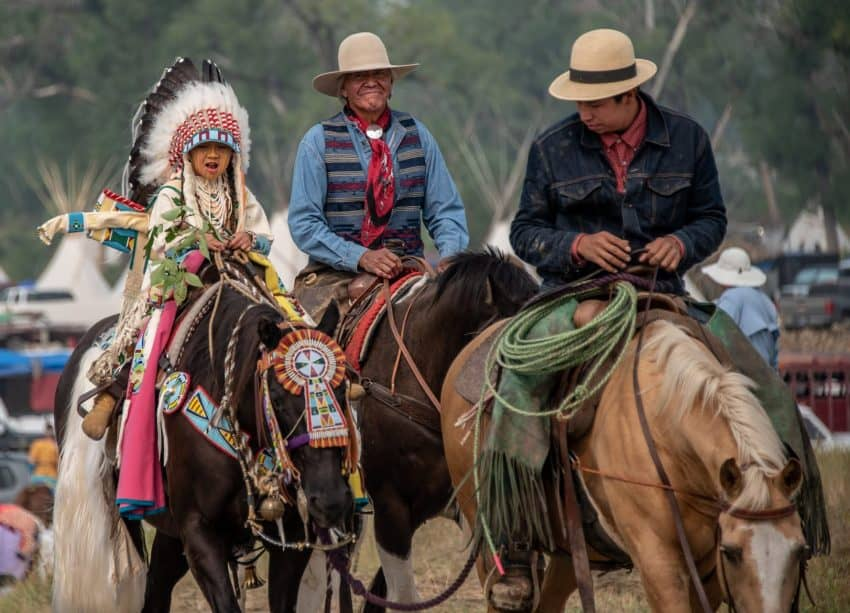 Young riders in the Crow Fair parade will have an elder riding with them for safety reasons. In this photo, three generations of a Crow family take part in this time-honored tradition.