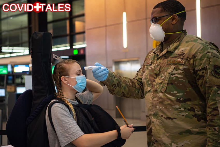 Senior Airman Kevin Gray II, 62nd Aerial Port Squadron passenger service specialist, takes the temperature of a passenger traveling to Asia at the Seattle-Tacoma International Airport in Seattle, Wash., April 30, 2020. Passengers with a fever of 100.4 degrees or higher are denied travel as a precaution against the spread of COVID-19. (U.S. Air Force photo by Senior Airman Tryphena Mayhugh)