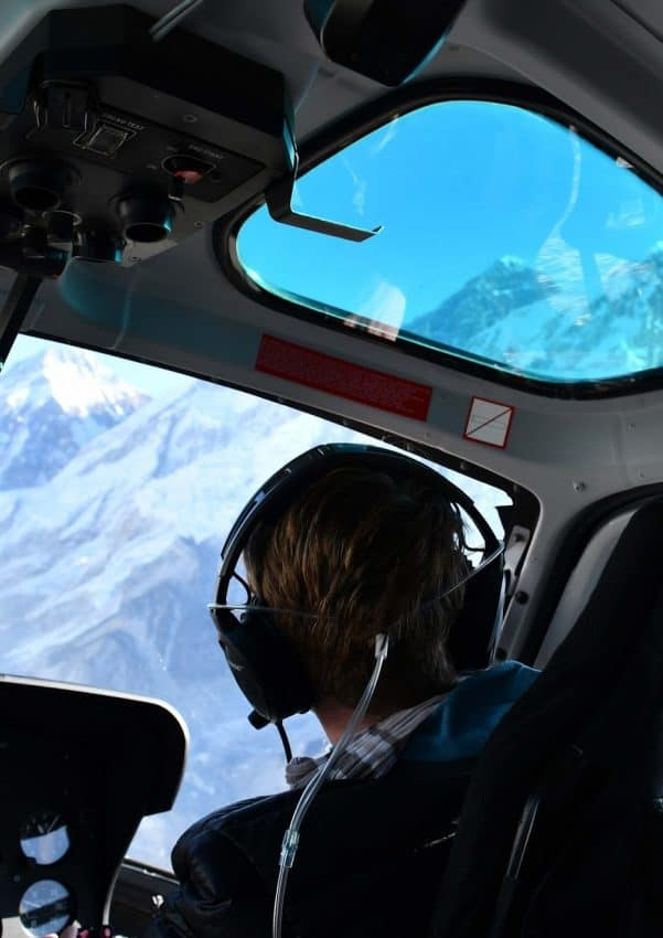 Our first glimpse of Everest. seen through the blue roof window. The plastic tubes around Lawrence's head, supply him with oxygen in the helicopter..