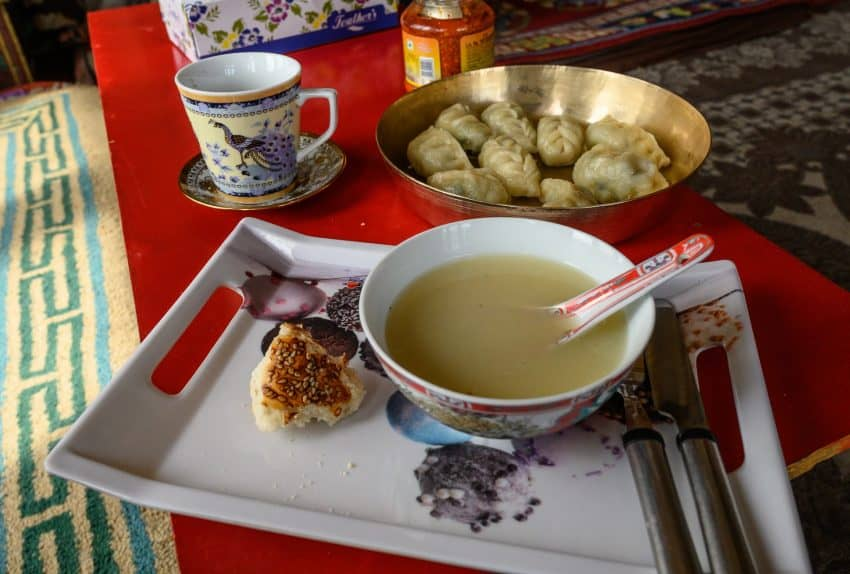 Homemade meat-stuffed momos and a tasty broth, served with tea and biscuits, made for a satisfying lunch in the company of newfound friends.