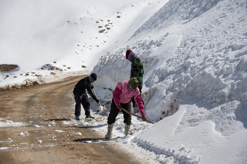 Random groups of workers shovel snow on the Khardung La Pass. The purpose of this effort is unknown.