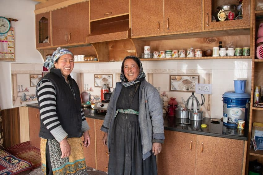 Tensin's mother and auntie stand in the kitchen/main room of their simple dwelling. Like most locals, they wear cold-weather clothing both indoors and outside.