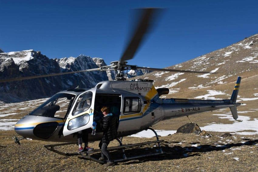 Struck with altitude sickness, Lawrence helps one of the Indian businessmen. We jumped in and out of helicopters at least 6 times, including visiting an alpine restaurant for breakfast, ($25 US) so the much wanted front seat was shared.