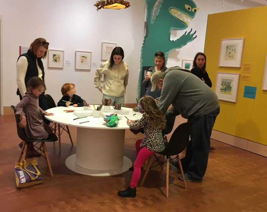 Budding illustrators gather round a table at the Eric Carle Museum of Picture Book Art.
