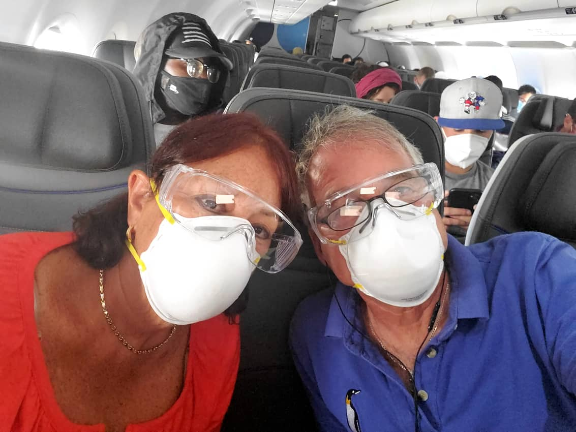 Tab and Maureen Hauser onJet Blue wearing a mask and eye protection.