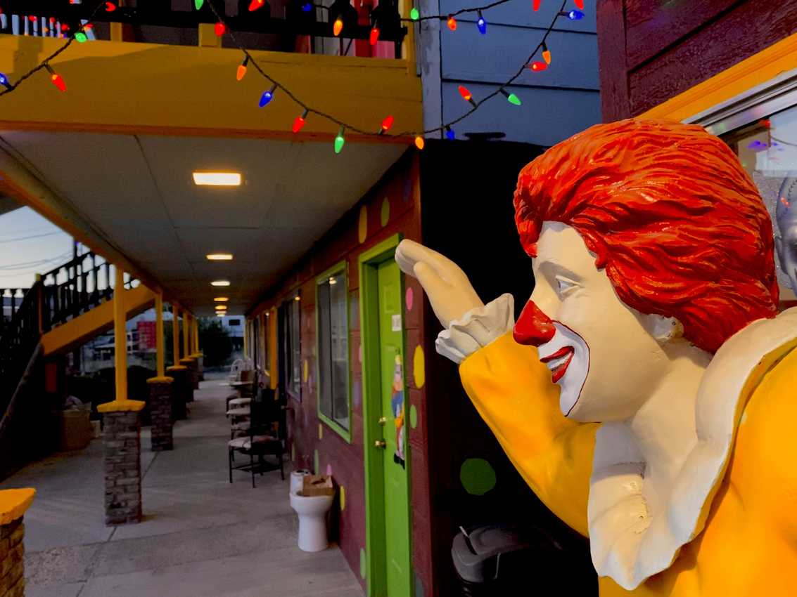 Aglow at dusk, unsettling smiles welcome guests to the Clown Motel, dubbed Creepiest Motel in America.