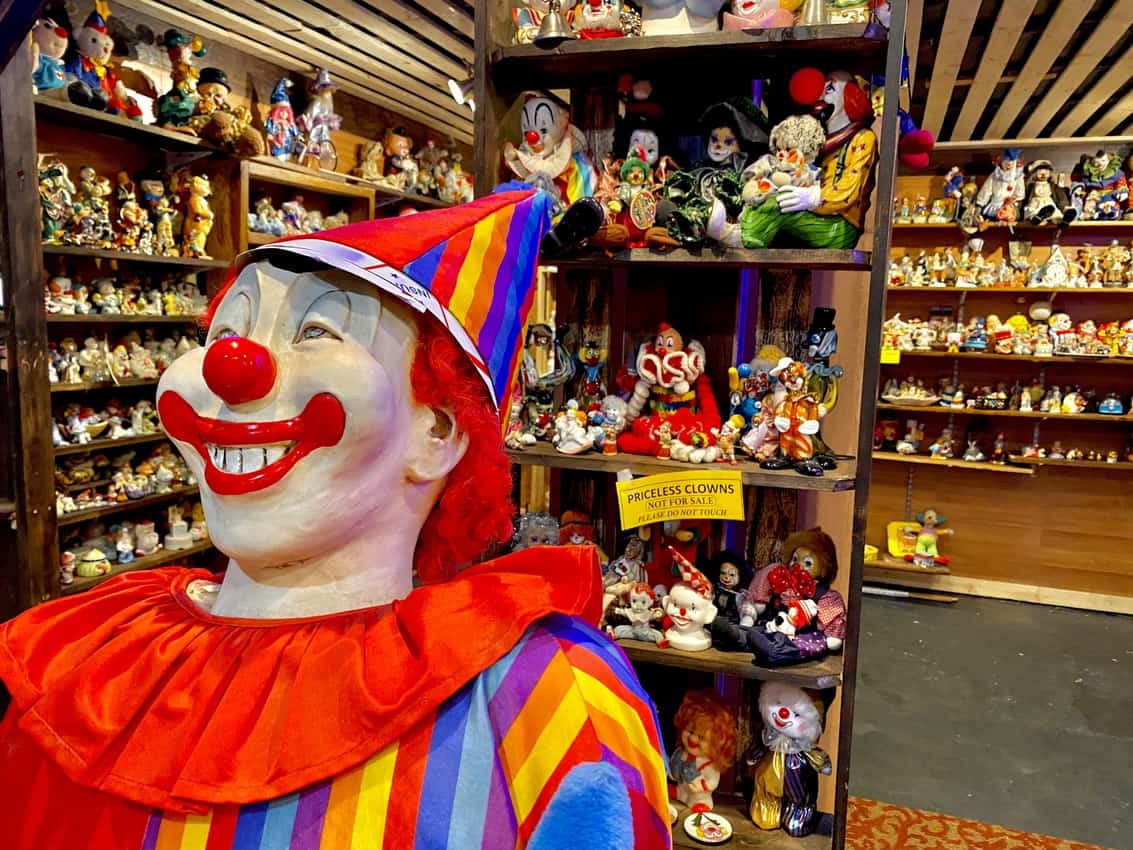 A haunting menagerie of costumed jesters cram museum shelves, where the world's largest collection of clowns may be greeted just beyond the motel's lobby.
